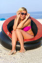 Joyful girl sitting in an inflatable chair on the beach Stock Photos
