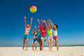 Joyful girls playing volleyball group of young on the beach Royalty Free Stock Photography