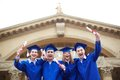 Joyful graduates group of ecstatic students in graduation gowns holding diplomas Stock Photo