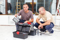 Joyful handy men and their tool boxes handymen with box starting work in houses Royalty Free Stock Photography