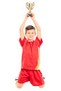 Joyful little boy holding a trophy above his head isolated on white background Stock Photo