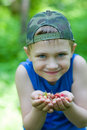 Joyful little boy holding a wild strawberry Stock Photo