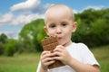 Joyful little boy with pleasure eats chocolate Royalty Free Stock Photo