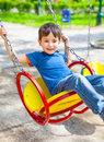 Joyful little boy swinging on a swing sunny day Royalty Free Stock Photo