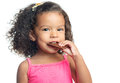 Joyful little girl with an afro hairstyle eating a chocolate bar isolated on white Royalty Free Stock Photography