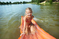Joyful little girl on mattress in lake at summer Royalty Free Stock Image