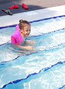 Joyful little girl swimming in the pool. Stock Photos