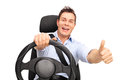 Joyful man driving and giving a thumb up