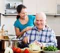 Joyful mature couple cooking food in kitchen Stock Photography