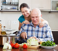 Joyful mature couple cooking food with vegetables in home kitchen Stock Image