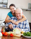 Joyful mature couple cooking food with vegetables in kitchen Stock Photo