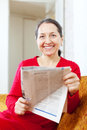 Joyful mature woman with newspaper sits on sofa at home Stock Photos