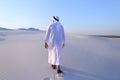 Joyful Muslim man walks on top of desert with smile on face on c