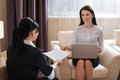 Joyful pleasant woman giving a hotel maid her employment contract Royalty Free Stock Photo