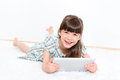 Joyful pretty little girl laughing as lies her stomach white carpet playing modern digital tablet white room Royalty Free Stock Photo