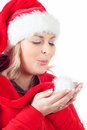 Joyful pretty woman blowing in red santa claus hat Royalty Free Stock Images
