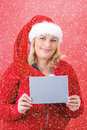 Joyful pretty woman in red santa claus hat smiling with snowflakes Stock Image