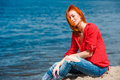 Joyful redhead woman sitting comfortably and smiling looks serene free enjoying a sunny day at the beach Royalty Free Stock Photos