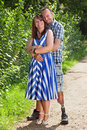 Joyful romantic young couple standing hugging each other on a rural path with a handsome disabled amputee with a prosthetic leg Royalty Free Stock Images