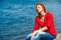 Joyful serene redhead woman sitting comfortably feeling and free and enjoying a sunny day at the beach Royalty Free Stock Photography