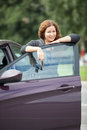 Joyful smiling caucasian woman standing behind car door with key Stock Photography