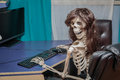 Joyful smiling skeleton in a wig sitting in chair behind the desktop computer Royalty Free Stock Photo