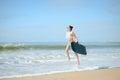 Joyful surfer girl happy cheerful going surfing at ocean beach running into water. Female bikini woman heading for waves