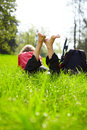 Joyful tourist enjoying relaxation lying barefoot in green grass outdoors summer park Royalty Free Stock Images