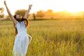 Joyful woman in a field wearing white dress rice after harvest thailand Royalty Free Stock Image