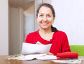 Joyful  woman fills in payment documents Royalty Free Stock Photos