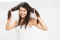 Joyful woman playing with her hair beautiful young long brunette running fingers through the tresses as she lifts it away from Royalty Free Stock Photo