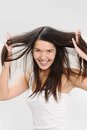 Joyful woman playing with her hair beautiful young long brunette running fingers through the tresses as she lifts it away from Stock Images