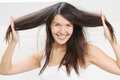 Joyful woman playing with her hair beautiful young long brunette running fingers through the tresses as she lifts it away from Stock Photo