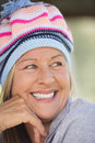 Joyful woman with warm beanie hat in winter outdoor portrait attractive mature to keep head happy relaxed smiling blurred Royalty Free Stock Images