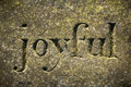 Joyful the word etched in a old weathered stone Stock Image