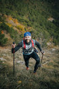 Joyful young athlete climbs a mountain with nordic walking poles Royalty Free Stock Photo