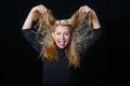 Joyful young blond woman is playing with her hair Royalty Free Stock Photo