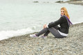 Joyful young girl sitting on pebble beach by the sea on a cloudy cold day Royalty Free Stock Photo