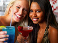 Joyful young girls smiling and holding  drinks Stock Photos
