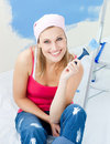 Joyful young woman holding a paint brush smiling Royalty Free Stock Images