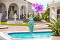 Joyful young woman jumping into the pool while holding a bunch of balloons
