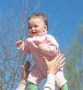 Joyfulness cheerful baby in the hands of the mother against the sky Royalty Free Stock Photography