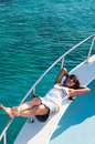 Joyous brunette woman in synglasses laying on deck caucasian shipboard of yacht Stock Photography