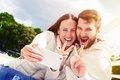 Joyous couple outdoors photo of showing peace sign and taking selfie by mobilephone Stock Photography