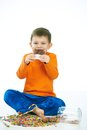 Joyous kid eating chocolate sitting cross legged little on floor sweets spilt isolated on white Stock Images