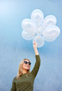 Joyous young female model with balloons shot of caucasian woman in sunglasses against blue background Royalty Free Stock Image