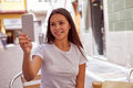Joyously smiling young girl taking pictures pretty in a street cafe while wearing her hair loose and casual clothing Royalty Free Stock Image