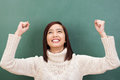 Jubilant asian student cheering in elation attractive young raising her fists the air her excitement against a green Stock Image