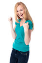 Jubilant woman cheering and celebrating beautiful vivacious raising her fists in the air at her successful Stock Photos
