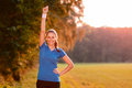 Jubilant young woman punching the air with her raised fist as she celebrates a success while standing in lush green countryside in Stock Photos